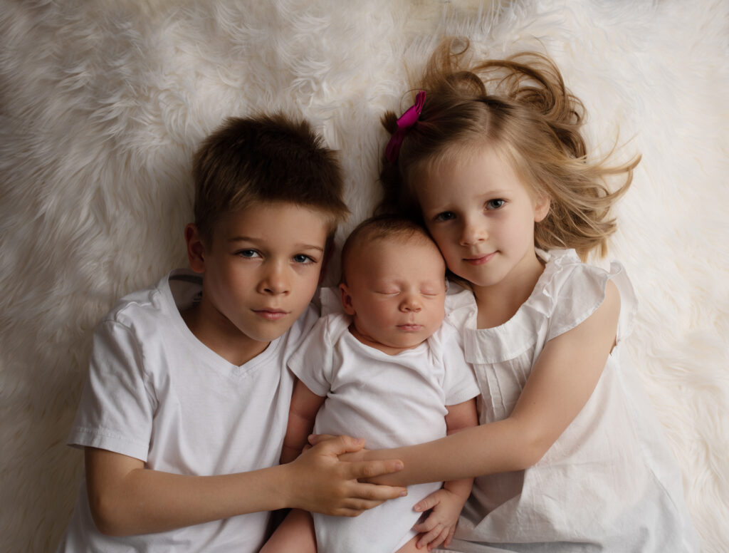 siblings holding, hugging newborn brother
