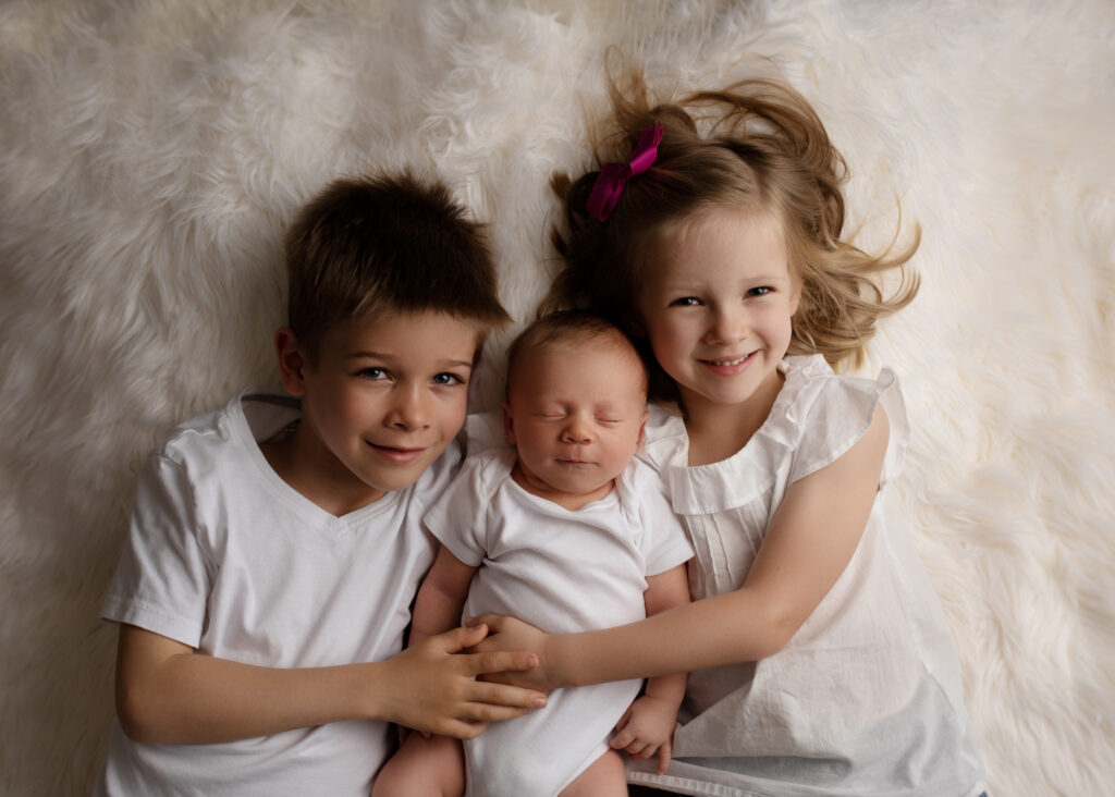 siblings laying on the bed, holding newborn baby brother