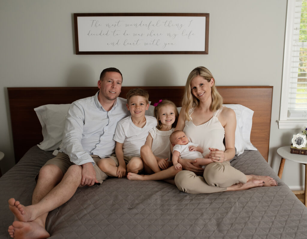 family of five sitting on the bed, mom holding new baby, hugging