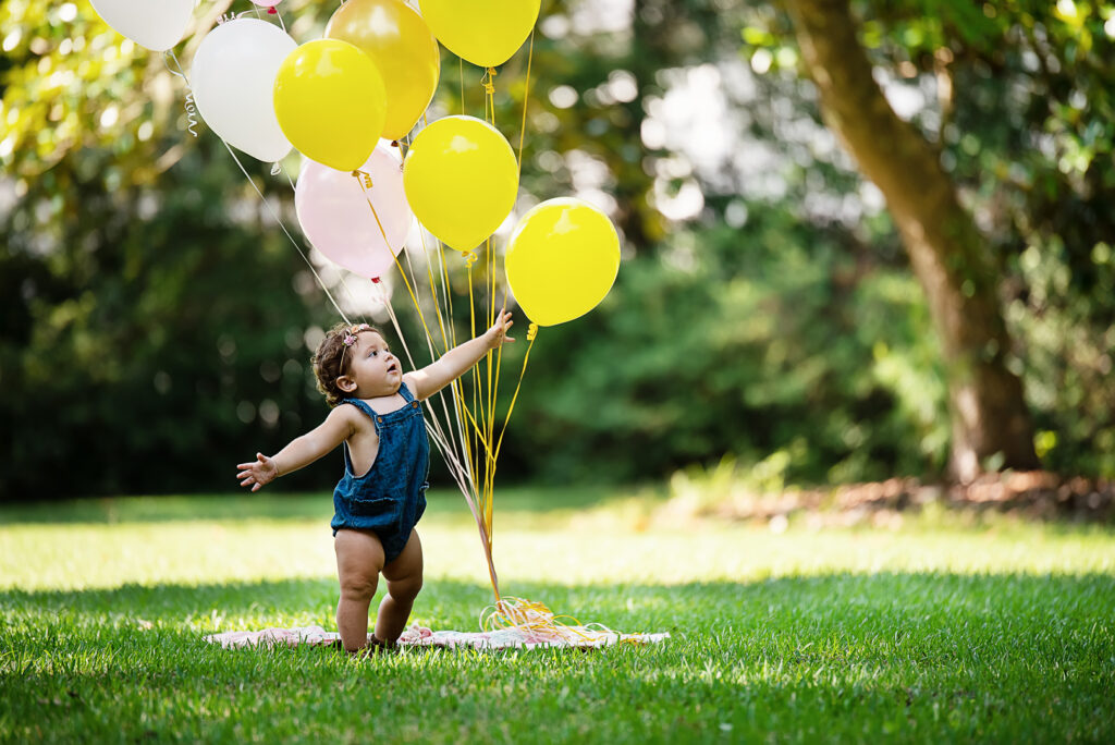 baby reaching ballons