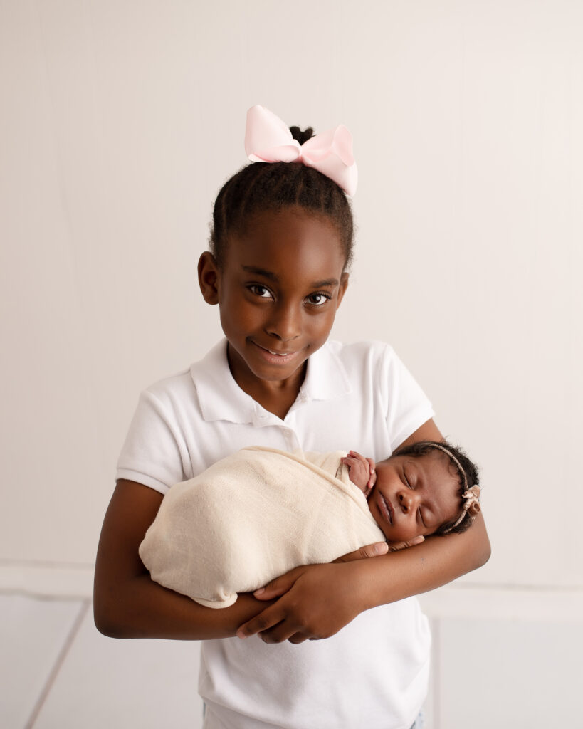 sibling holding newborn baby